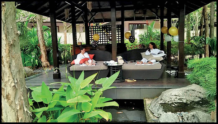A Couple get soothing spa on the beautiful Restaurent Covered with full of Plants.
