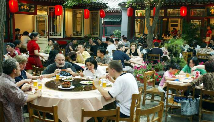 Group of Chinese people sitting and eating food in a Chinese Hotel.